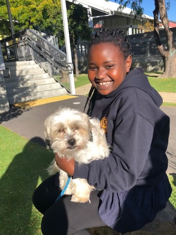 One female student sitting in the school yard with a fluffy dog