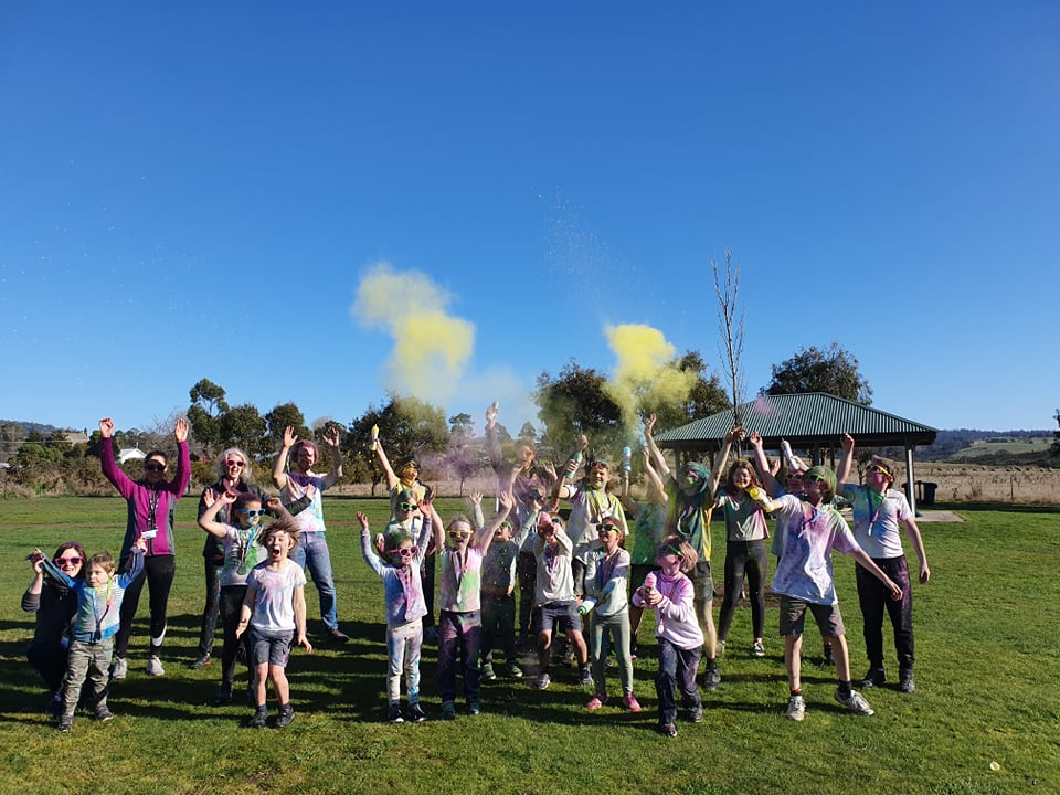 Photo of a group of happy students and some adults with their hands up in the air. They are covered in paint